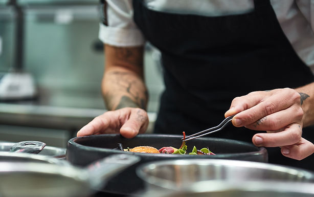 A chef adding finishing touches to a dish