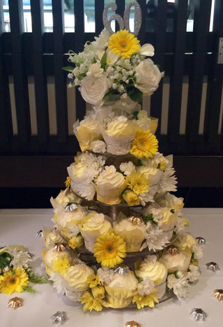 60th birthday cupcake tower in yellow and white colour theme with fresh flowers