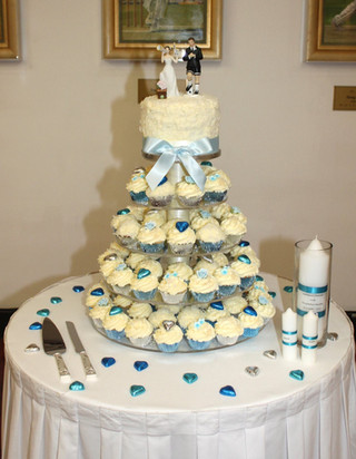 Wedding cupcake tower in a blue and white theme with small cake and soccer cupcake topper