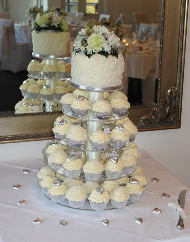 Classic white wedding cupcakes in a silver and white theme with small cake and fresh flowers