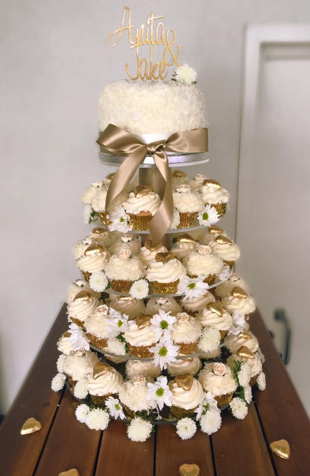 Gold and white wedding cupcake tower with small cake and fresh flowers