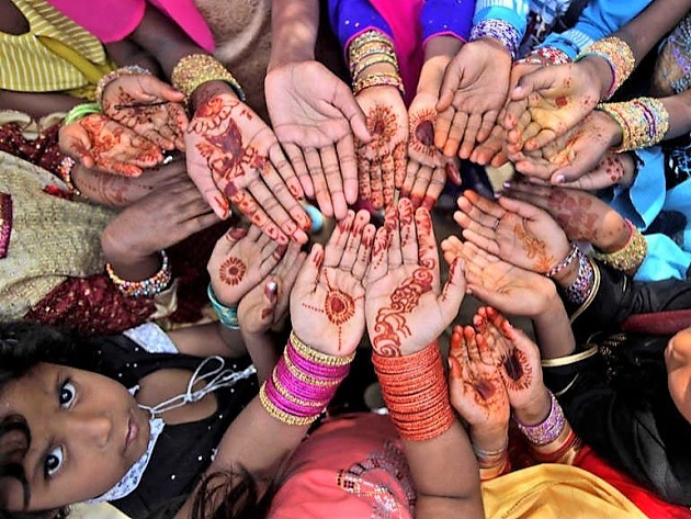 Christian girls paint their hands with henna paste in preparation for the Easter holiday.
