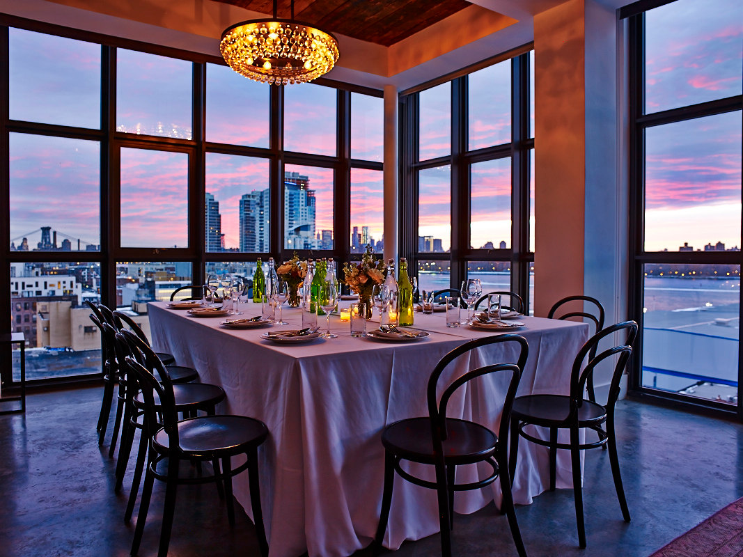 Loft Dinner Table with long white table linens and black bentwood chairs in front of floor to ceiling windows and dusk sky