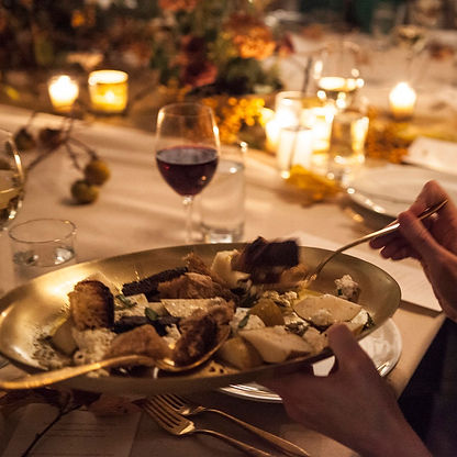 Plate of food with womans hands holding it and glass of red wine with lots of candles and floral in background