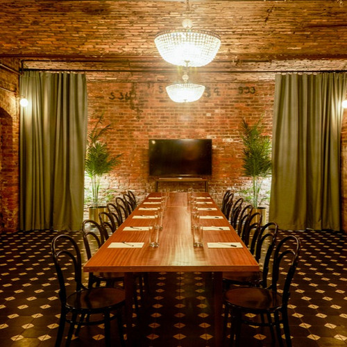 Long wood table with black bentwood chairs set for a warm intimate meeting with TV at back of room