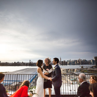 Wedding Ceremony with couple holding hands on terrace overlooking NYC east river and skyline