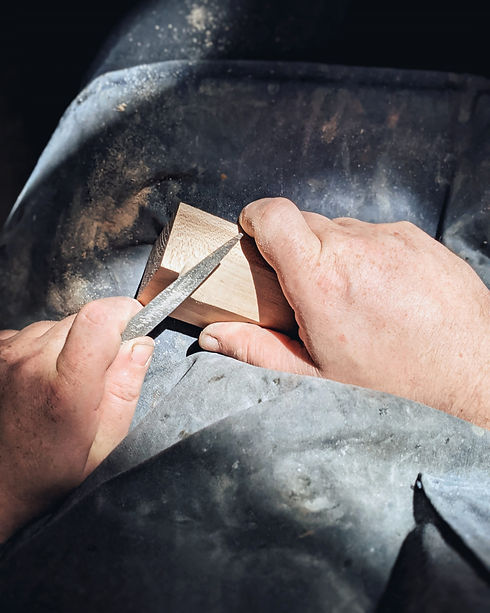 two hands using a file on a piece of maple wood on an apron covered lap