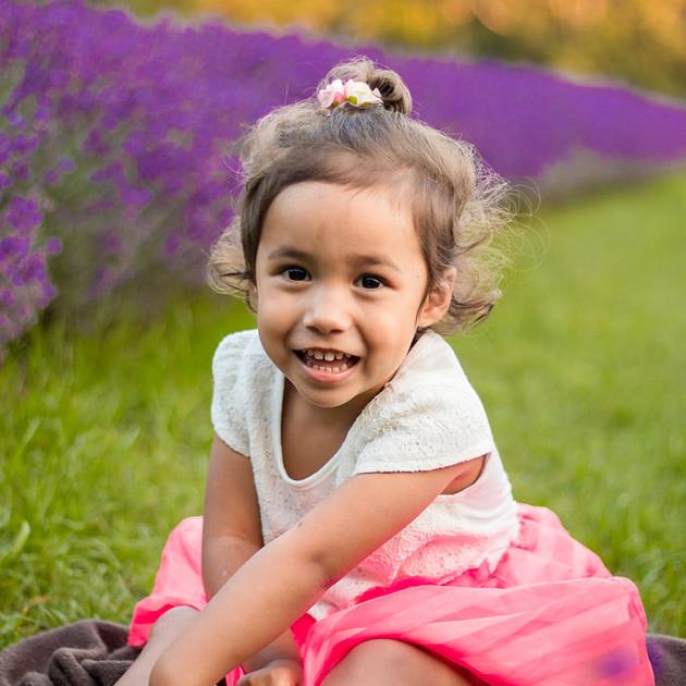 portrait of little girl sitting in lavender field