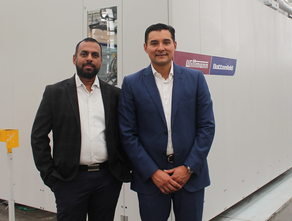 Ananth Pathmanathan (general director of APG México) and Rodrigo Muñoz general director of Wittmann Battenfeld de México), together with the injection molding machine with the highest tonnage in the plant, a MacroPower of 2,400 tons.