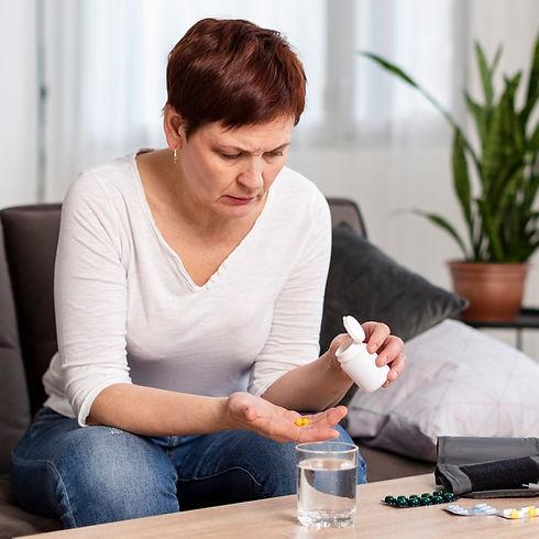 vista-frontal-da-mulher-tomando-pilulas_