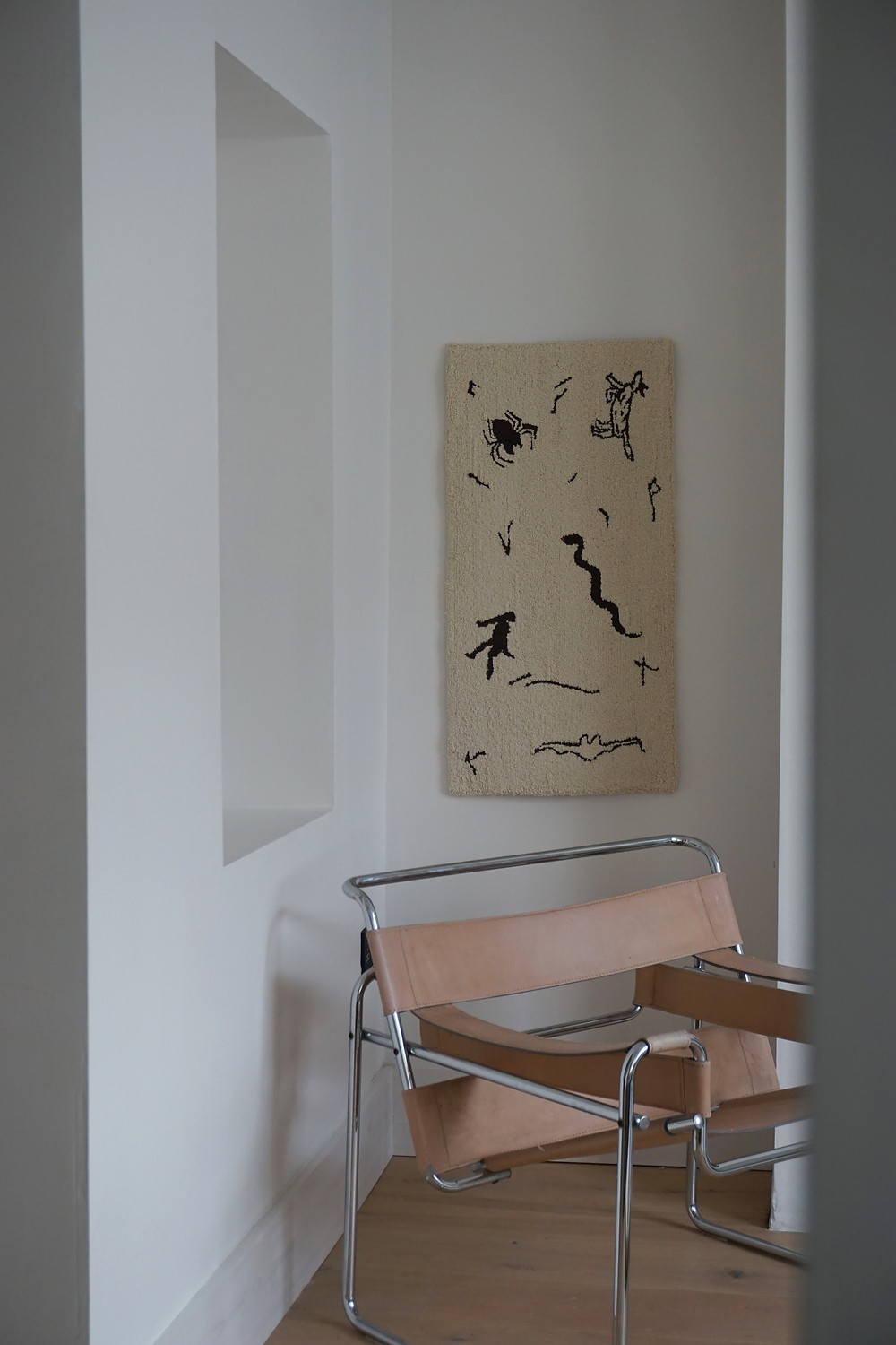 Walling hanging handmade tapis featuing a man, a bat, a bug, a dog, a fish and a snake