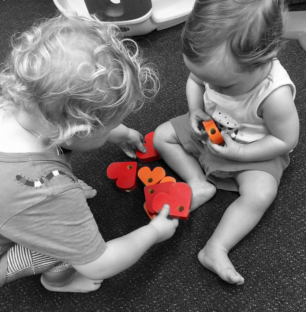 Members of the toy library play with heart shaped blocks