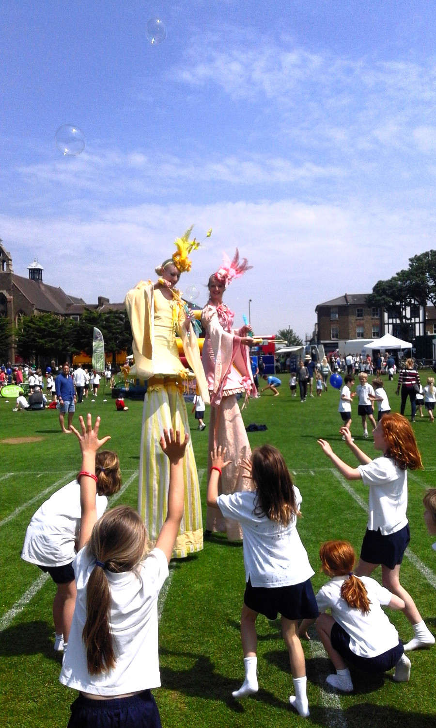 The Ladies Circus Stilt Walkers Blowing Bubbles in South London