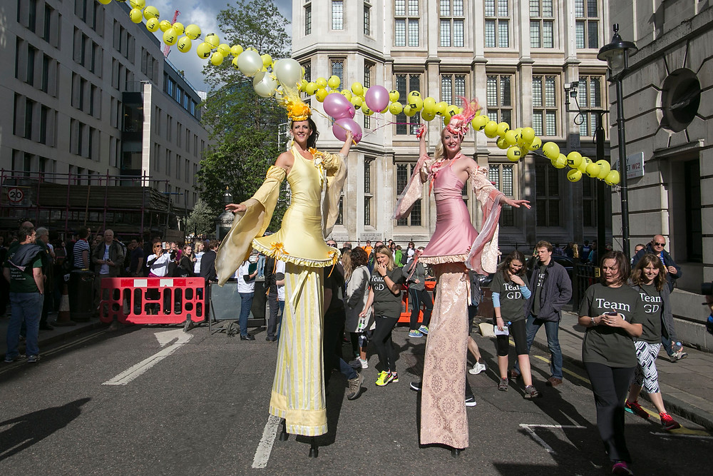 The Ladies pink and yellow stilt walkers with balloons