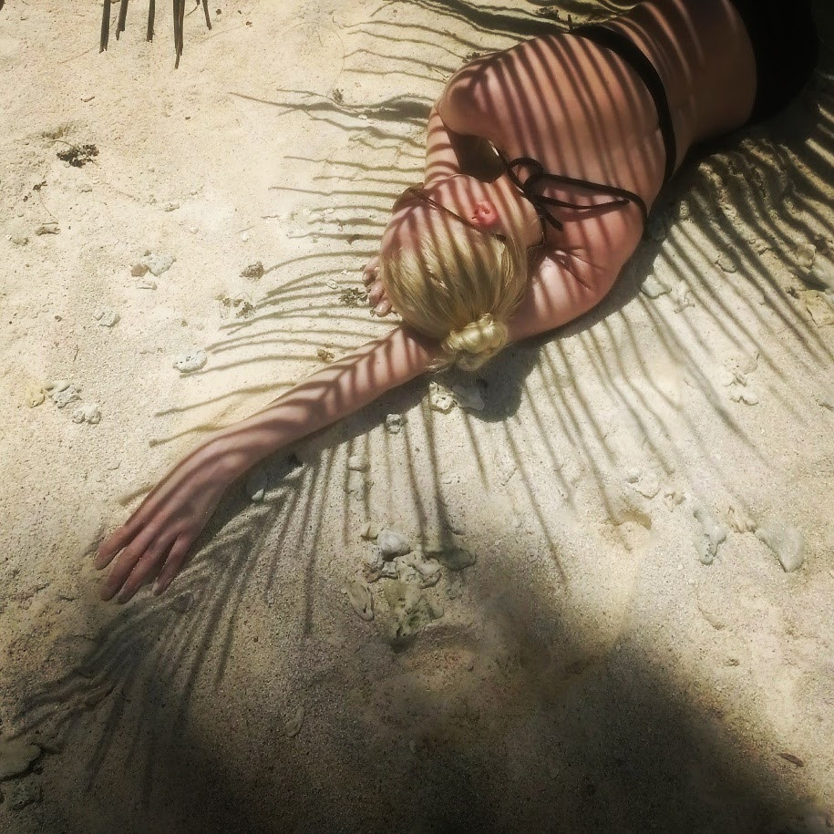 Katie Hardwick on the beach with a palm tree shadow in the Seychelles