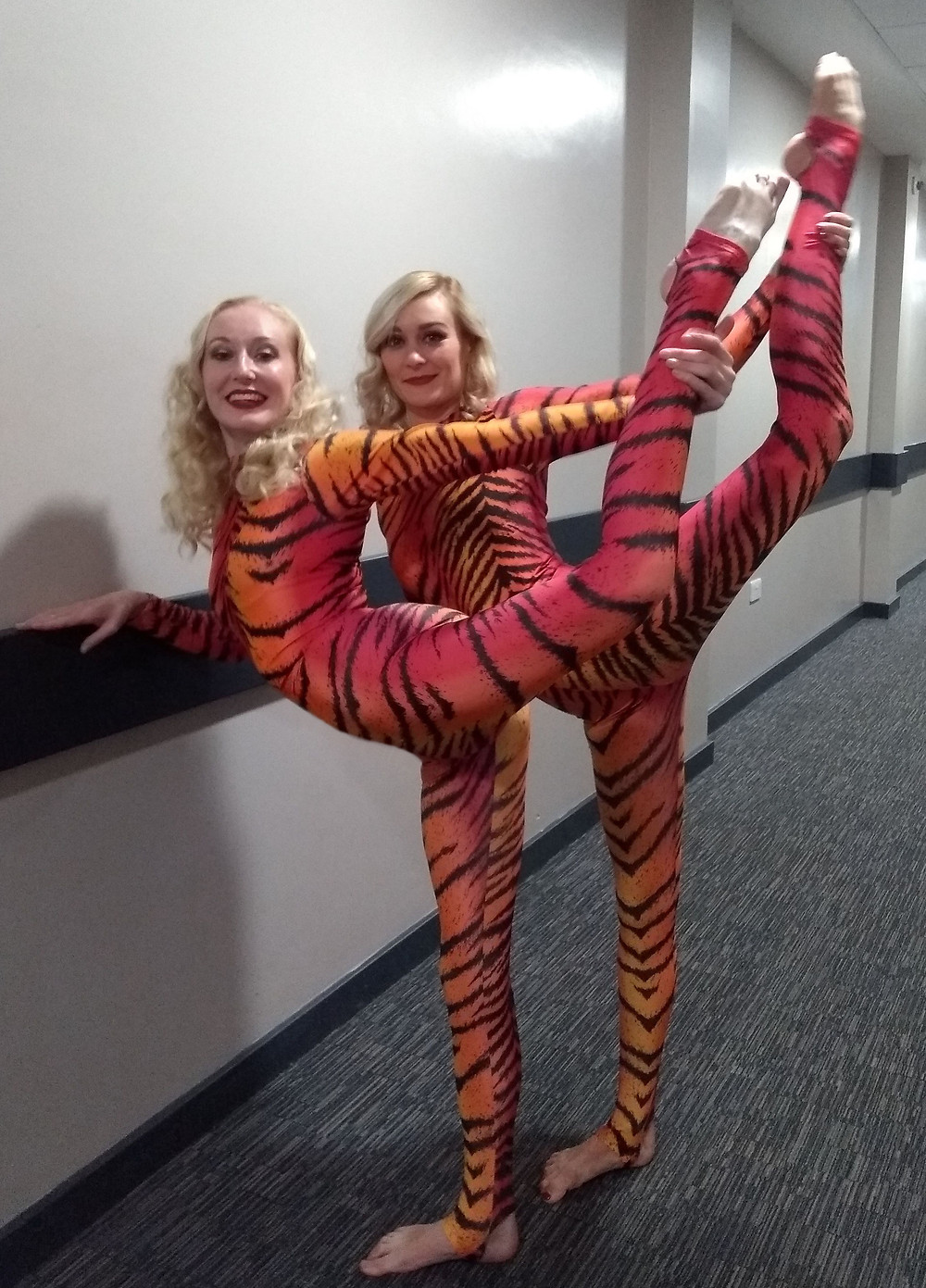 Two aerialists backstage, posing in pink-orange tiger catsuits
