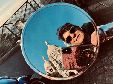 View from the sideview mirror of a Vespa