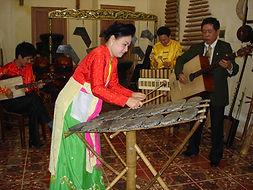 Mai Lien playing dan da, Hanoi. Photo In