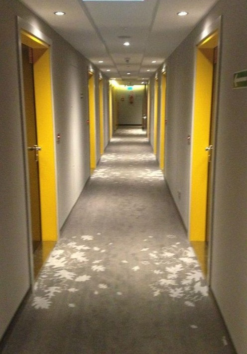 A hallway design reflecting biophilic concepts in the carpet pattern.  The bright yellow of a sunny day adds to the biophilic concept. And the yellow helps break up the hallway ength