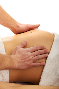 Pregnant woman having a massage on her b