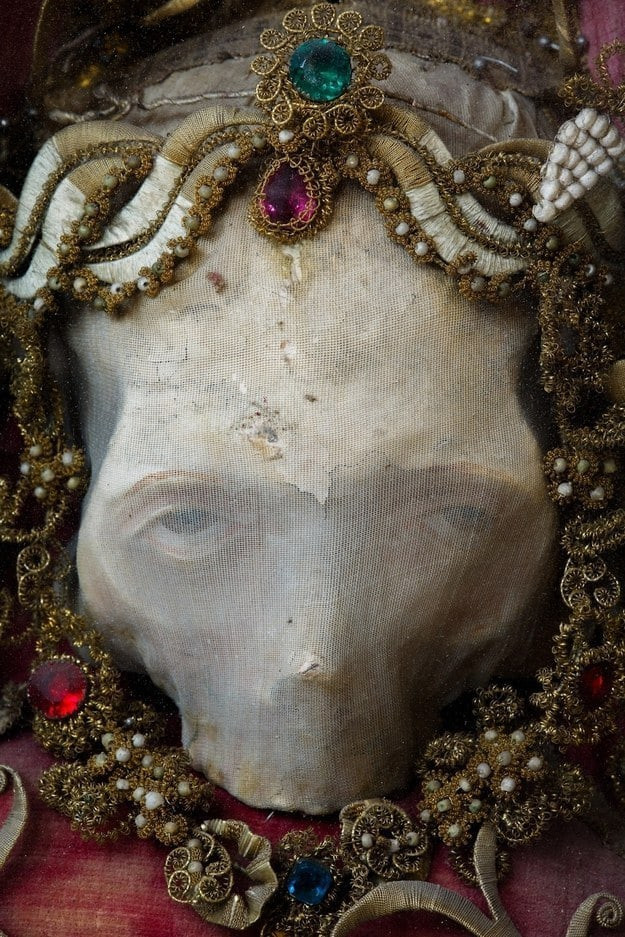 color picture of corpse face wrapped in a shroud with a crown of jewels