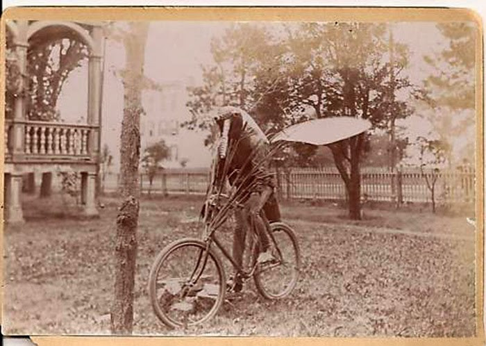black and white photo of person in an insect costume including wings riding a bicycle