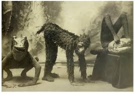 old black and white photo three people in costume a frong squatting a monkey on hands and feet and the third bent on a table