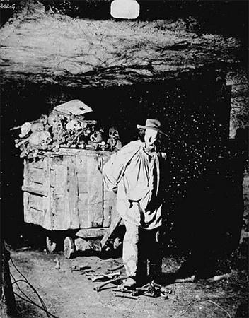 grainy black and white photo of a bedragged man in an underground mine pulling a cart overflowing with human bones