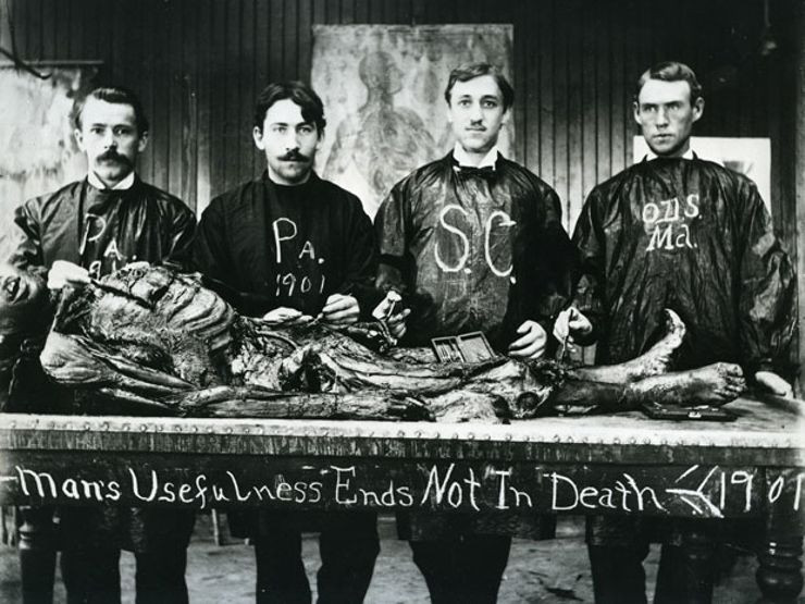 black and white photo medical students with dissected corpse in front of them text reads Man's Usefulness Ends Not In Death 1901