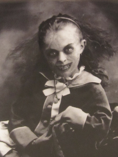black and white photo of a child with a demon face