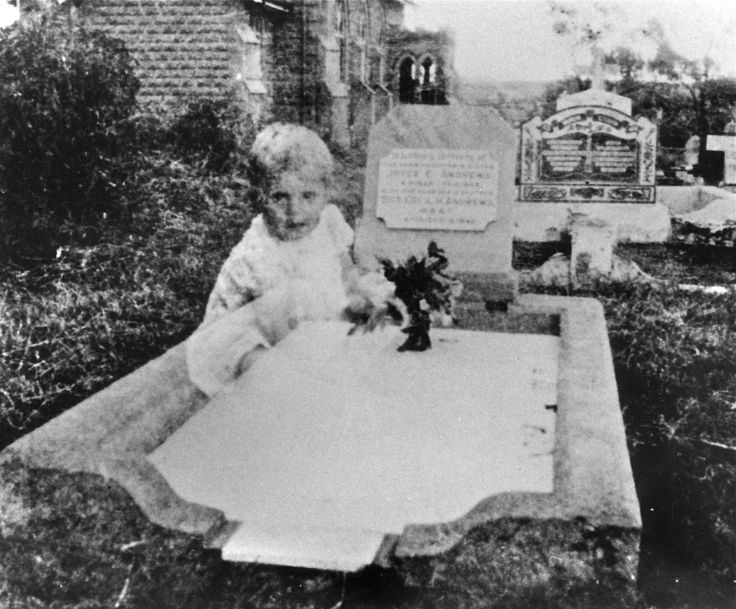 black and white photo of a gravesite with transparent baby ghost sitting on grave