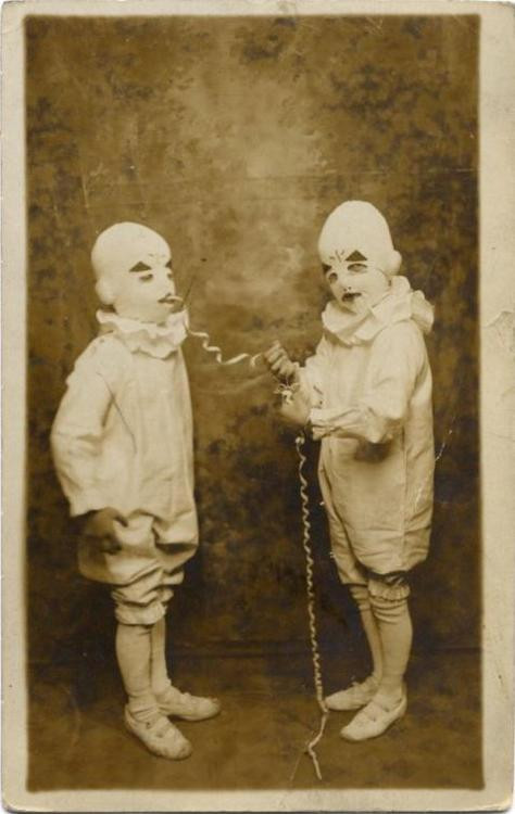 very grainy tintype photo of two kids dressed as identical clowns, one pulling a long curled ribbon out the mouth of the other