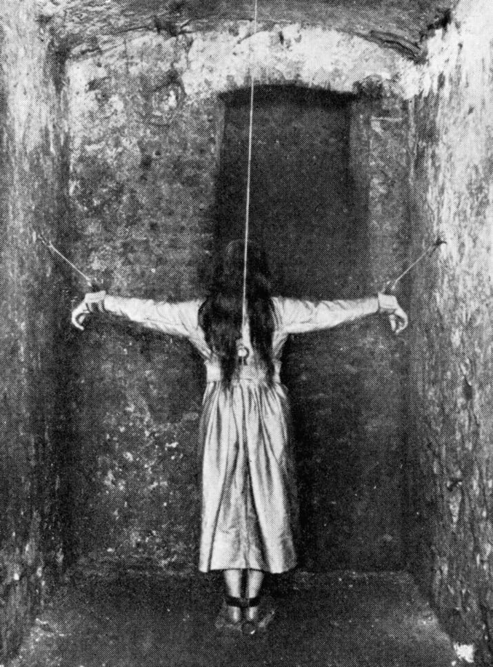 black and white photo of girl crusified with ropes in an insane asylum