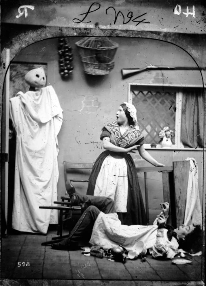 black and white photo ..of a play ..the pumpkin king wrapped in a shroud, and actress startled and an actor who has fallen backwand off his chair
