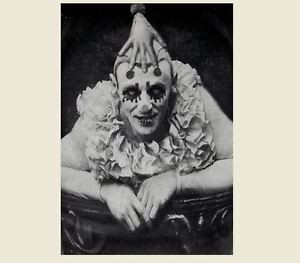 Old blak and white photo of a clowns face between a ruffle collar and a hand on his head