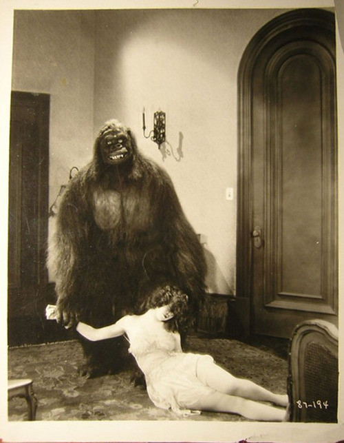 old black and white photo of a long haired gorilla draging a half naked woman