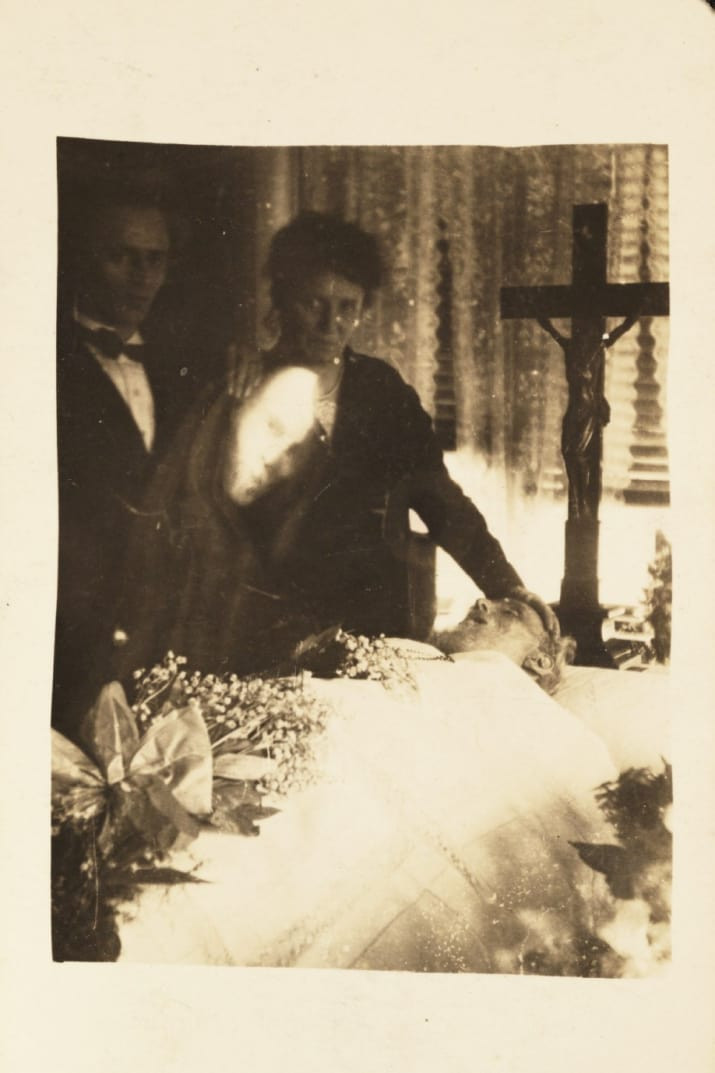 grainy black and white photo of ghost hovering over deceased in coffin