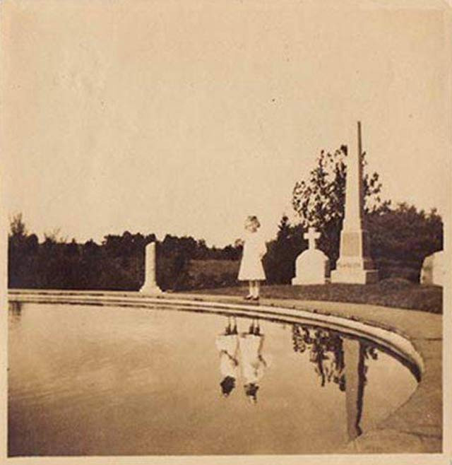 grainy black and white photo of one girl staring into a pond, two girls are refleced in the water there is a cemetery in the background