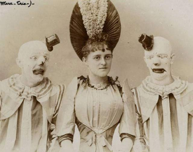 black and white photo of female circus performer with identical circus clowns on eigther side of her