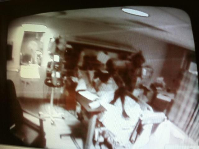 hospital security camera black and white ceiling view of a black shadow rising from a body on a gurney