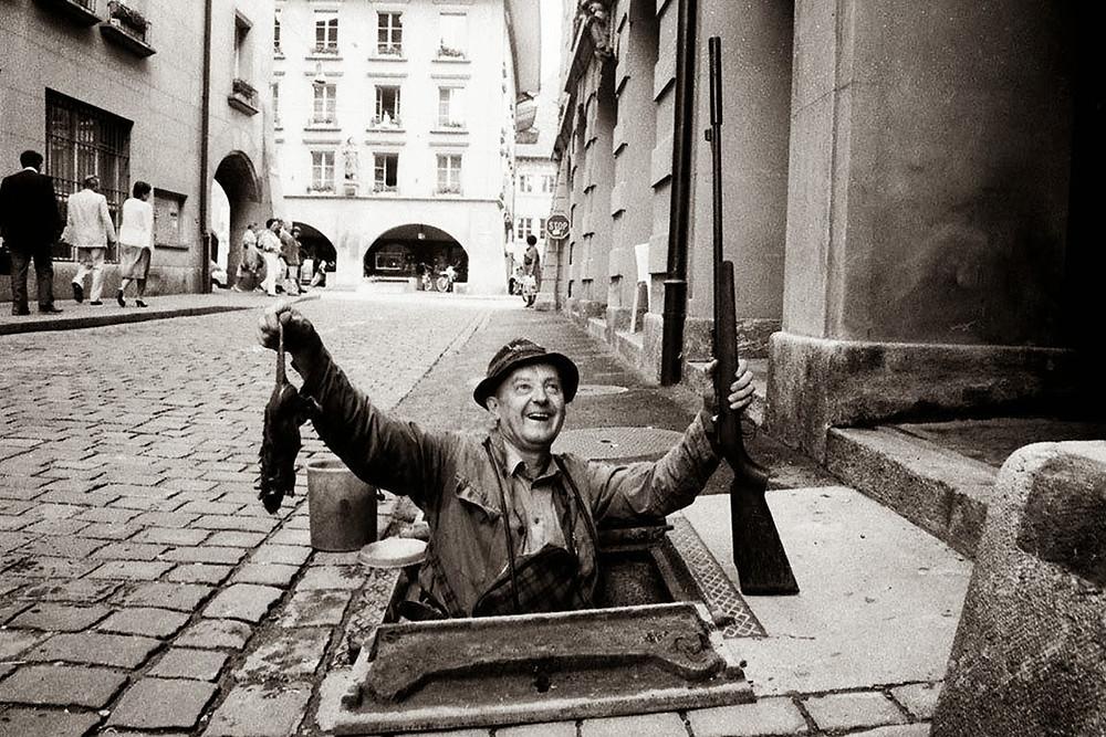 black and white of man coming out of sewer with a rifle in one hand the other hand holds up dead rats by the tails. titled rat catcher 1920
