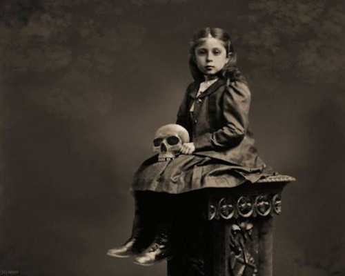 black and white of serious young girl on a pedistal holding a skull
