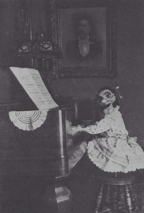 black and white photo of long chinned doll in a dress playing the piano