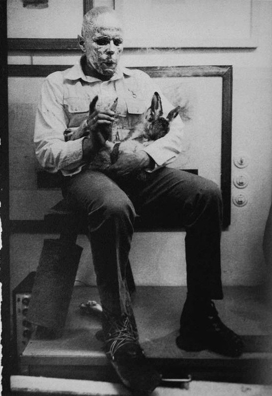 black and white photo of man with burned face seated holding an animal