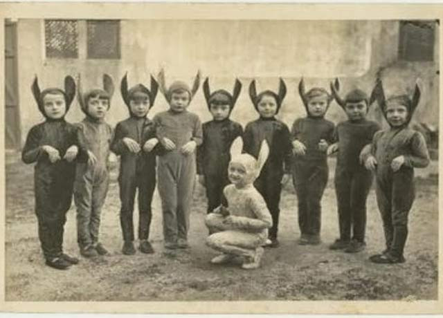 old black and white photo of 10 kids in bunny costumes  9 in dark coatumes standing in semi circle with light bunny kneeling in middle
