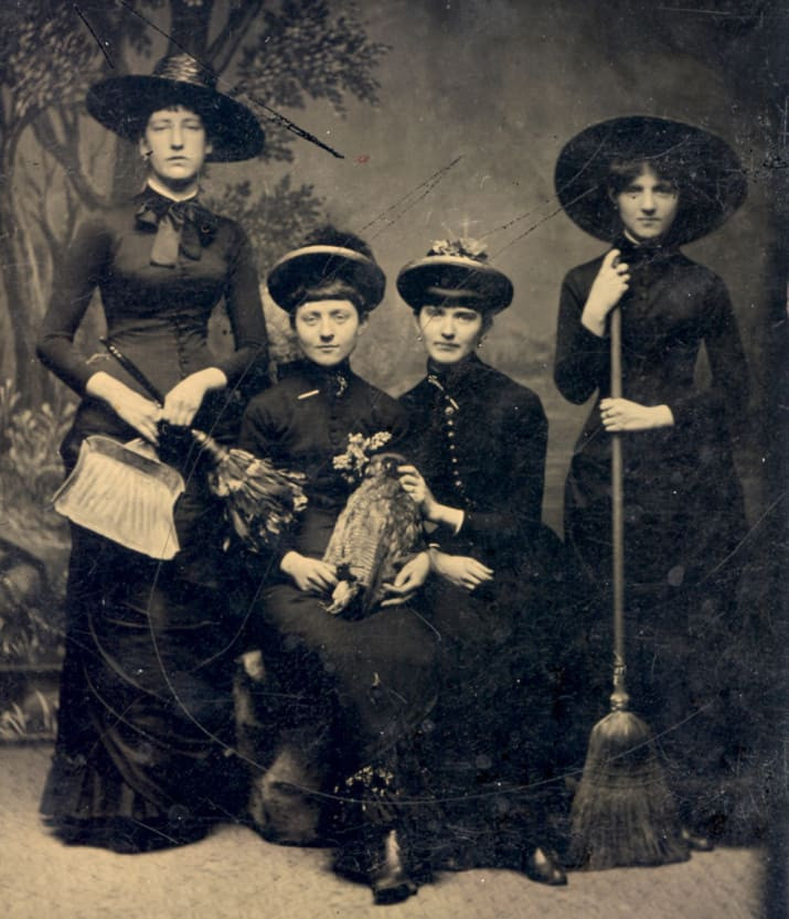 grainy black and white photo of 4 young women witches posing for the camera two on the end standing one holds a broom and the other a duster and dust pan the two seated between them are holding an owl