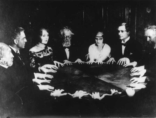 black and white photo of a seance circa 1890