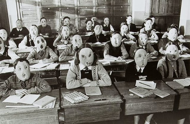 black and white photo of children at desks in classroom each one wearing a different creepy smooth mask