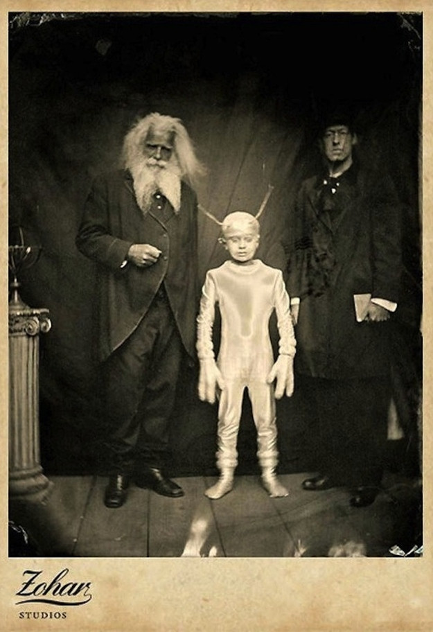 old black and white photo of two scolars posing with a very short person dressed in a very convincing alien costume standing between them