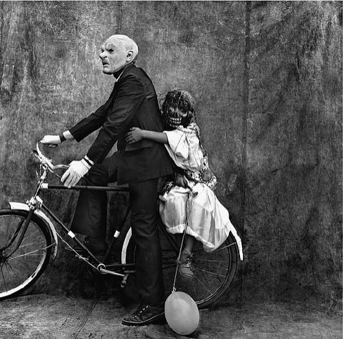black aand white photo of old bald disfaced man on bike with a child with a demon face riding sidesaddle on back wheel  a baloon drags th ground